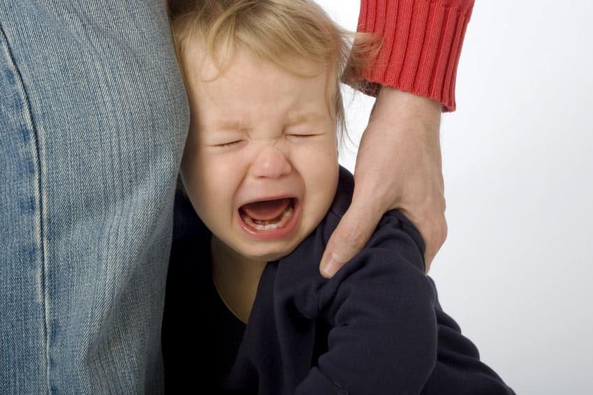 Hyperaktives Kind schreit an der Hand der Mutter